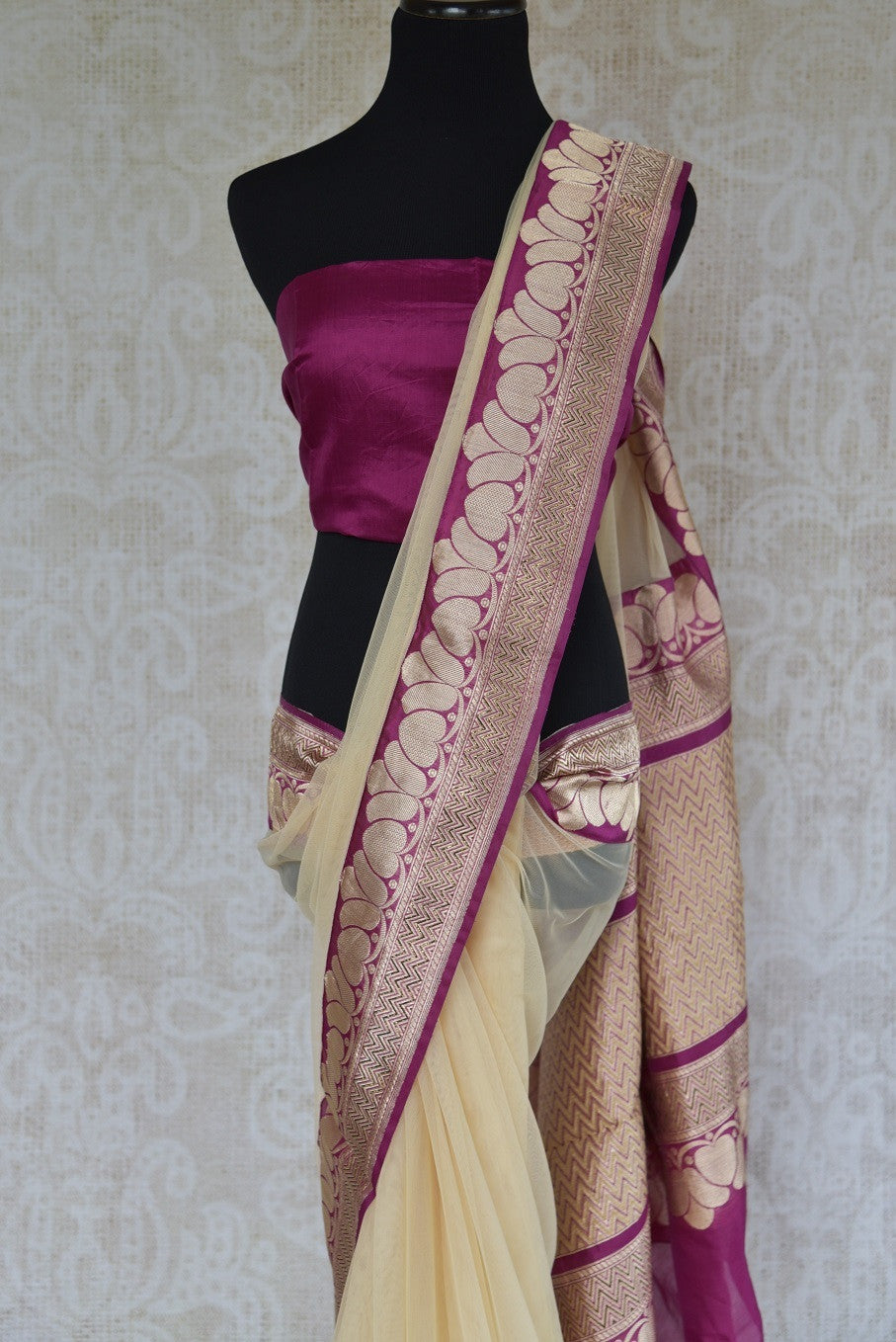 90C257 Net saree with a traditional Banarasi border. The cream and maroon saree from India can be bought at Pure Elegance - our Indian clothing store in USA. This elegant saree is sure to have you at the top of your ethnic style game.