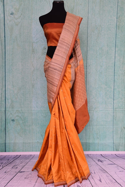 90C259 A half tussar & half Banarasi saree online at our Indian clothing store. The traditional orange sari with beige border makes for a great ethnic outfit for pujas and festive occasions. Buy this simple saree from Pure Elegance today!