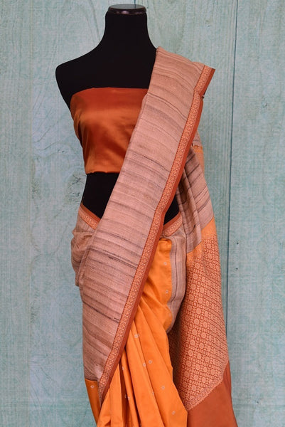 90C259 A half tussar & half Banarasi saree online at Pure Elegance - our Indian wear store in USA. The simple orange saree with thick beige border makes for a great ethnic outfit for pujas and festive occasions.