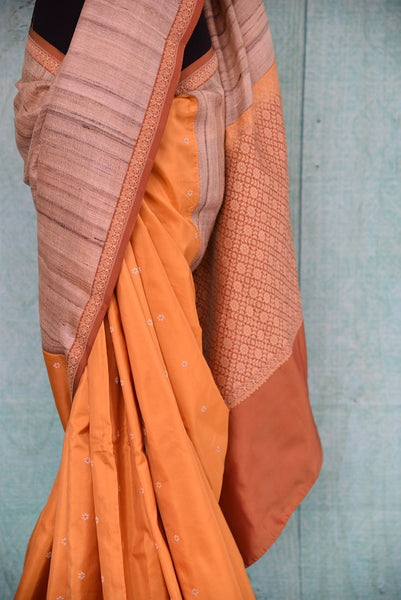 90C259 A half tussar & half Banarasi saree online at Pure Elegance, our Indian clothing store. The traditional orange sari with beige border is a great ethnic outfit for pujas and festive occasions.