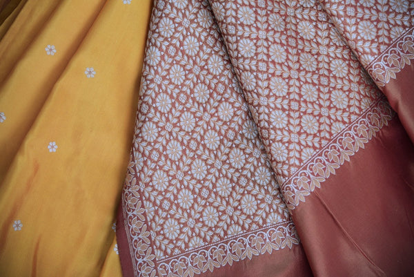 90C259 A half tussar & half Banarasi traditional Indian saree online at our ethnic clothing store. The plain sari with orange body and beige border makes for a great ethnic outfit for pujas and festive occasions.
