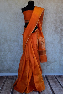90C283 A lovely matka silk saree in a beautiful hue of rust orange. The saree comes with a traditional floral zari pallu and is available at our online Indian wear store in USA.
