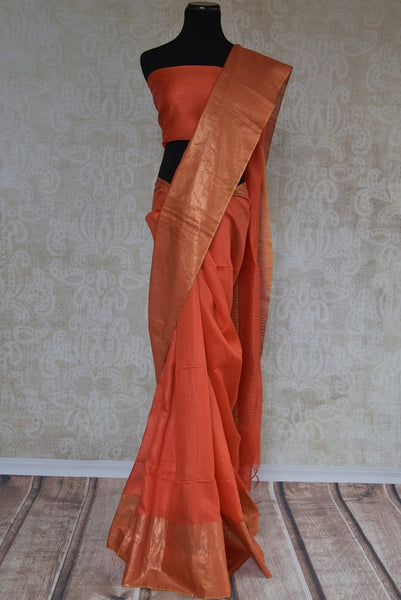 90C050 Simple orange Bhagalpur tussar saree with a gold zari border available at Pure Elegance. The Indian saree is perfect for parties, pujas & for festive occasions. The plain saree is versatile and can be dressed up in very many ways.