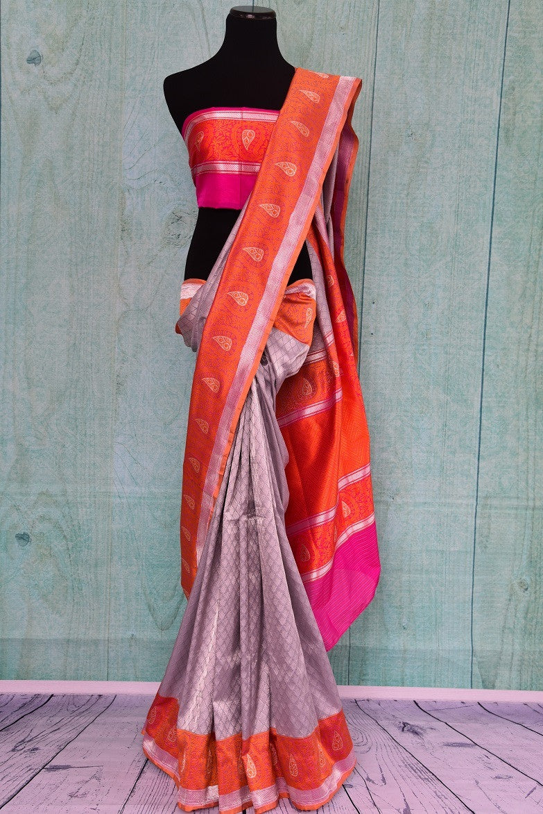 90C249 Silver grey traditional Banarasi silk saree from India with a vibrant orange border and pops of pink. Buy this charming saree online in USA from our ethnic wear store Pure Elegance.