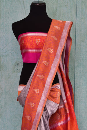 90C249 Silver grey traditional Banarasi silk saree with a vibrant orange border and pops of pink. Buy this Indian saree online in USA from our store Pure Elegance. A refreshing color combination with traditional elements - this saree is not to be missed.
