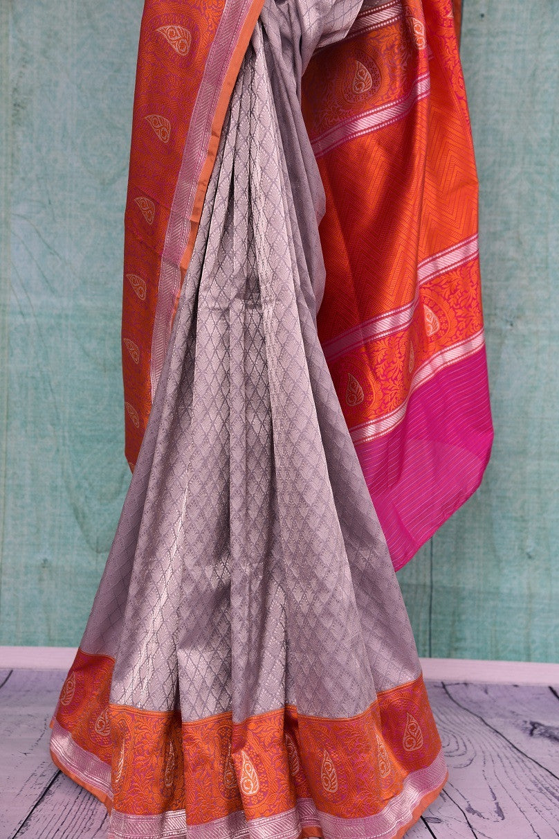 90C249 Silver grey traditional Banarasi silk saree with a vibrant orange border and pops of pink. Buy this Indian saree online in USA from our store Pure Elegance. This pleasing saree is a must-have for the coming season!