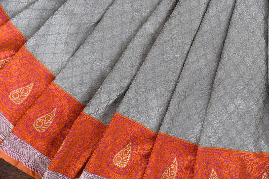 90C249 Silver grey traditional Banarasi silk saree with a vibrant orange border and pops of pink. Buy this Indian saree online in USA from our store Pure Elegance. This lovely saree is a wonderful pick for pujas and festive occasions.