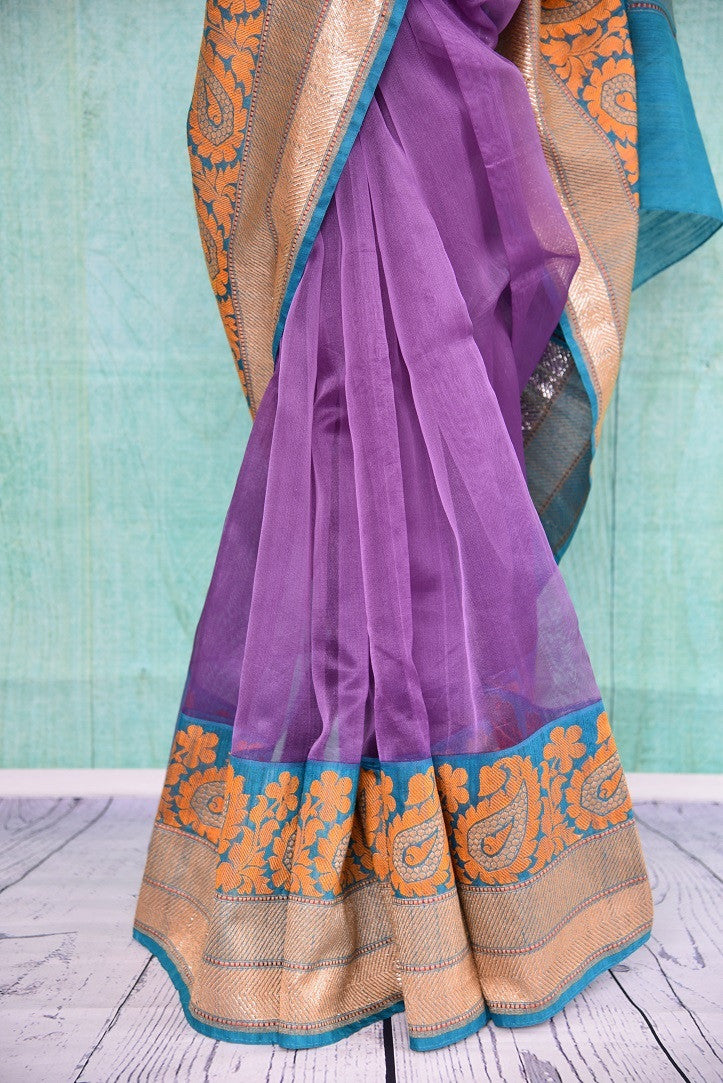 90A407 Purple saree with pops of orange & blue. The traditional Indian saree can be bought online at our Indian clothing store - Pure Elegance. The organza Benarasi saree for sale online is sure to keep all eyes on you!
