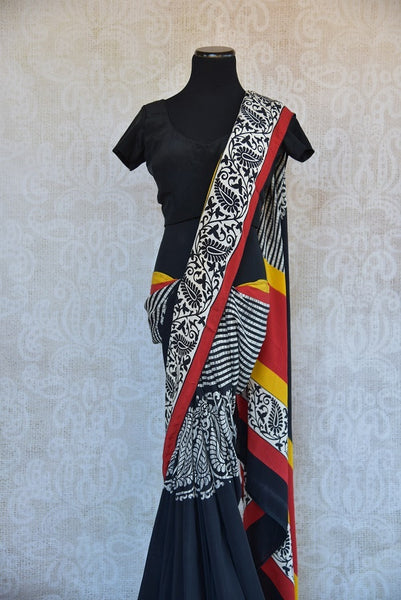90B491 Traditional printed saree available online in USA at our ethnic wear store Pure Elegance. The red and black crepe sari with pops of yellow and red is an ideal Indian outfit for small Indian functions and pujas. Buy this classic sari today!