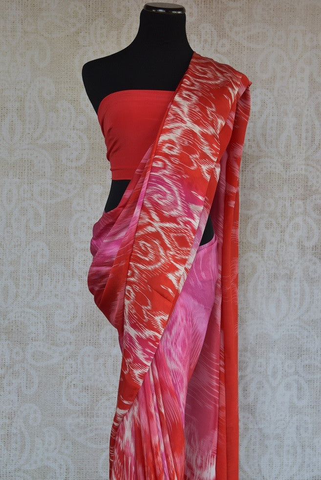90C177 Lovely pink, red and white printed saree available at our Indian wear store online in USA. The crepe silk saree is ideal for pujas and festive occasions. This ethnic outfit is a must-have for this season.