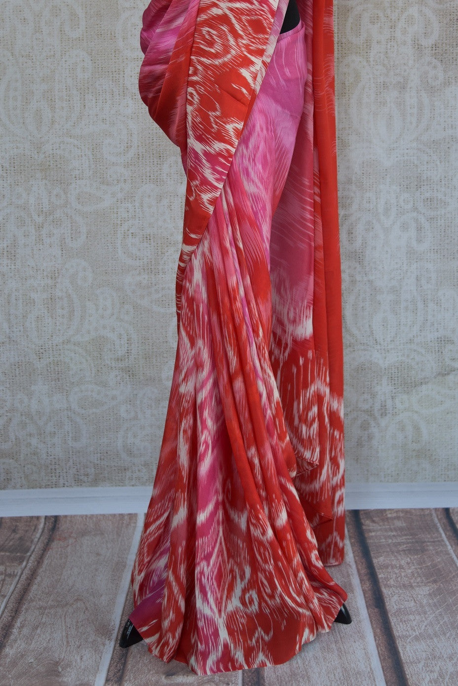 90C177 Lovely pink, red and white printed saree available at our Indian wear store online in USA. The crepe silk saree is ideal for pujas and festive occasions. This charming Indian outfit is sure to have you looking delightful!