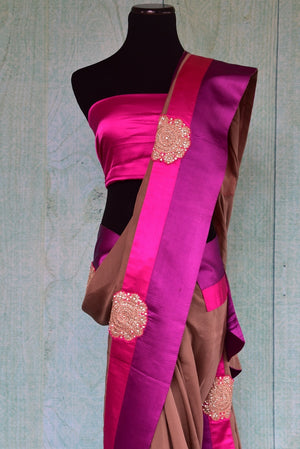 90B431 Buy this light brown Indian saree with pink & purple borders. The georgette saree comes with a satin blouse. This party wear Indian outfit is available in USA at our store Pure Elegance online & in Edison and will be the perfect addition to your Indian wear collection.