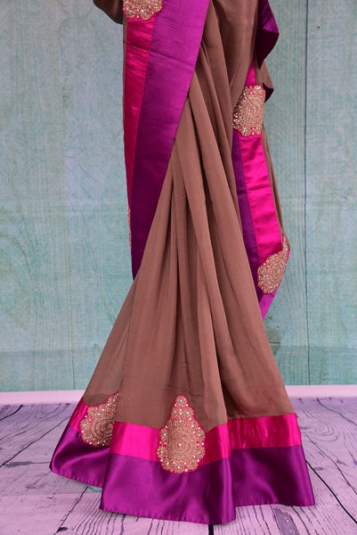 90B431 Buy this light brown georgette saree from India pink & purple borders and satin blouse. This party wear Indian outfit can be bought at our store Pure Elegance online & in Edison and will be the perfect addition to your Indian clothing collection.
