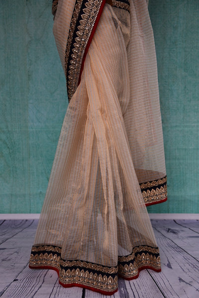 90B519 White zari kota sari from India with gold undertones and black & red border. Ideal for parties & weddings, this traditional saree can be bought at our ethnic fashion store Pure Elegance online or in Edison (USA).