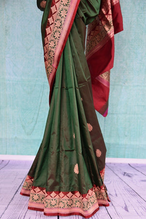 90A733 Traditional green saree with a classic red border is available at our online Indian clothing store in USA. The Banarasi saree is the perfect Indian wedding outfit. Buy this evergreen saree today!