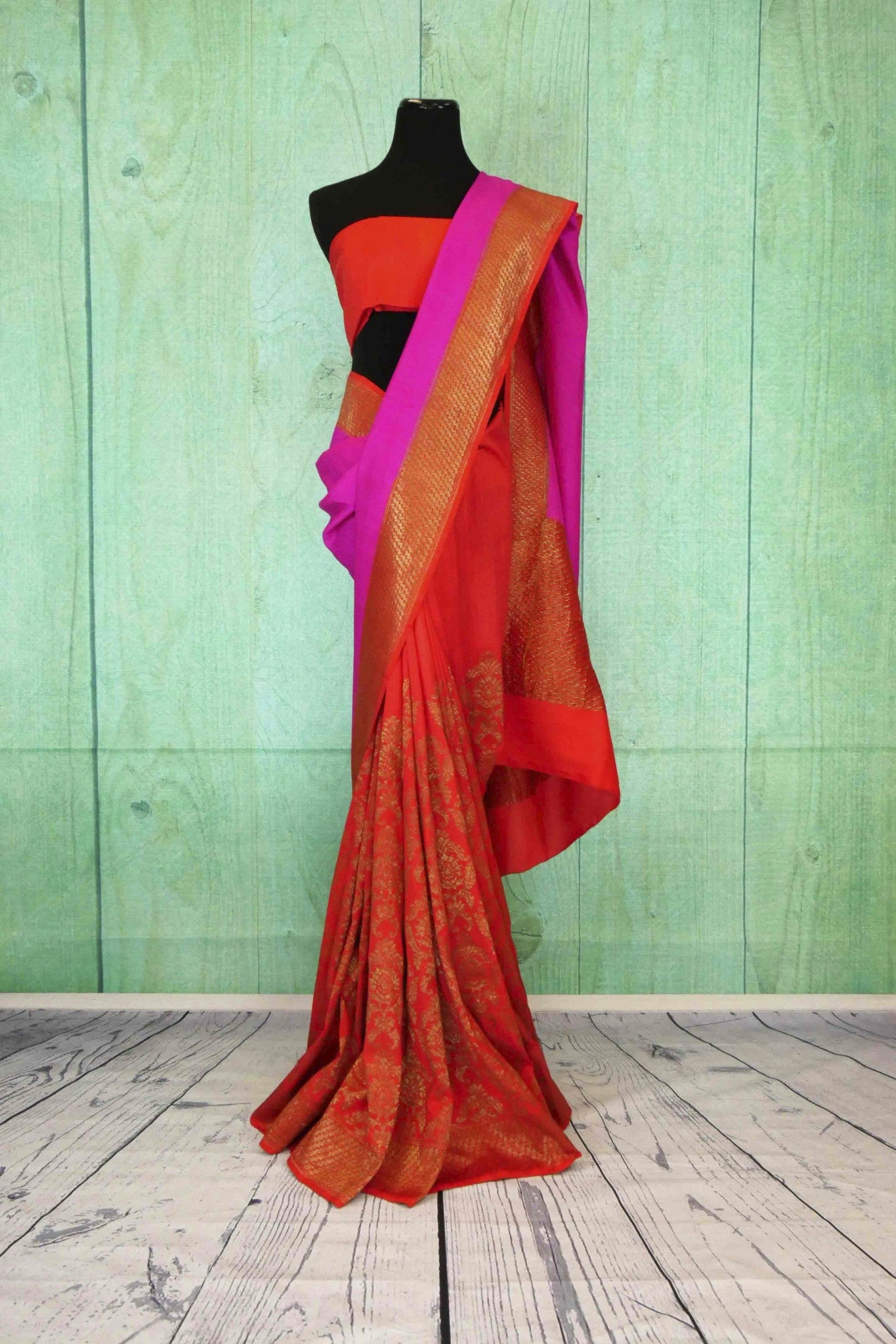 90C195 Traditional orange sari with golden pattern and pink trim. Buy this traditional georgette Banarasi saree in USA, ideal for ethnic functions and festivals, at our Indian clothing store - Pure Elegance.