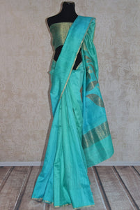 90C277 Buy this blue-green matka Banarasi saree online in USA at our Indian clothing store. Topped with a zari pallu, this Indian saree is ideal for festive occasions and pujas.