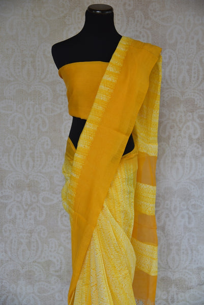 90B548 A tie and dye yellow, linen saree. The simple Indian outfit available at our ethnic wear store is perfect for pujas, festive occasions and functions. The shiburi printed sari will be a lovely addition to your ethnic clothing wardrobe.