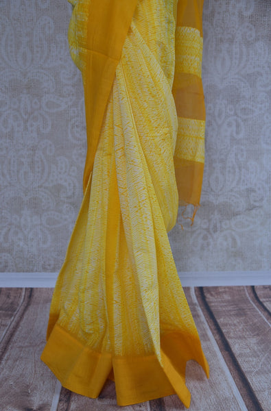 90B548 A tie and dye yellow, linen saree. The simple Indian outfit available at our ethnic wear store is perfect for pujas, festive occasions and functions. The shiburi printed sari is available online at Pure Elegance.