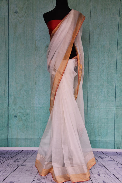 90B966 Traditional white zari kota saree with a gold border and red trim available online at Pure Elegance. The simple sari is a versatile classic that you can wear for many occasions.