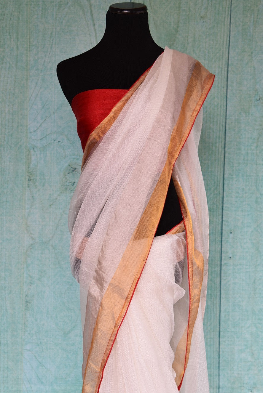 90B966 Look ethereal in this white zari kota saree with a gold border and red trim available online at Pure Elegance in USA. The simple sari is perfect for small Indian wedding functions and festive occasions.