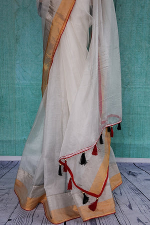 90B966 Lovely and plain white zari kota saree with a gold border and red trim available online at Pure Elegance. The simple sari with tassels on the pallu is wonderfully versatile and perfect for small Indian wedding functions and festive occasions.
