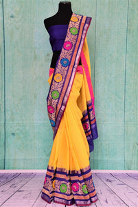 90B934 Yellow resham Banarasi saree with multi-color border and blue blouse. The traditional saree from India is available at our Indian clothing store online in USA. This ethnic outfit is perfect for several occasions including festivals, pujas and ethnic parties.