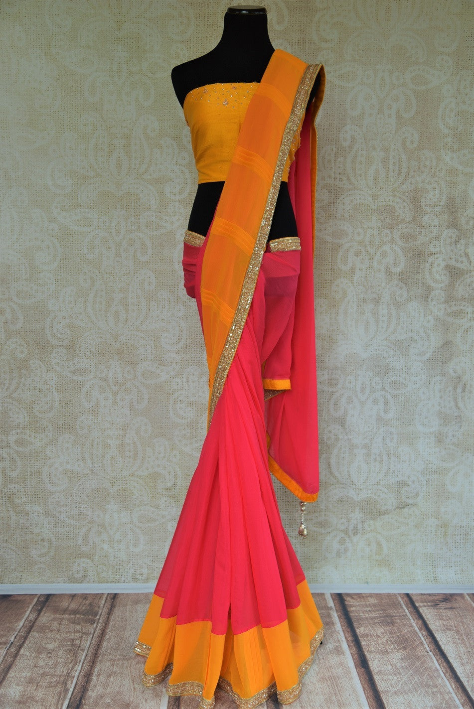 90B933 Pink & yellow sari with a metallic border. Buy this georgette party wear sari online at our Indian clothing store in USA & add it to your ethnic wear collection. The simple sari can be styled in many ways and is a versatile item.