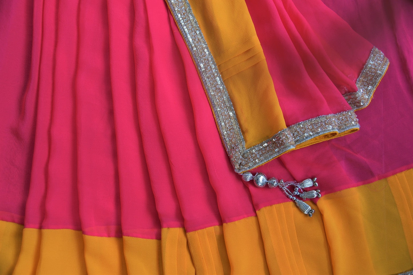 90B933 Pink & yellow sari with a metallic border. Buy this georgette party wear sari online at our Indian clothing store in USA & add it to your ethnic wear collection. The plain saree is wonderfully versatile and a faultless pick for many occasions like pujas and festivals.