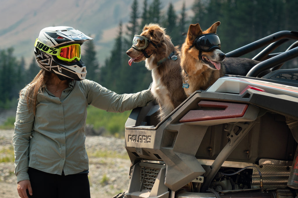 Woman stands next to two dogs wearing Rex Specs Dog Goggles on a Polaris RZR
