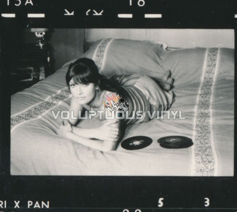 Marisa Mell lying on bed with vinyl records