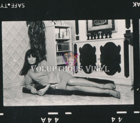 Marisa Mell laying down in front of liquor cabinet