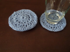 Crochet light blue round cotton coaster.