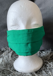 An African print face mask in shades of green. white and navy blue. The vivid Ankara print makes this green face mask the ideal addition to your outfit, to wear out and about to abide by government restrictions.