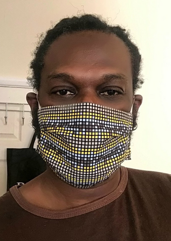 An attractive African print pattern, this Ankara grey face mask is made up of a gridded square pattern in monochrome shades and yellow.