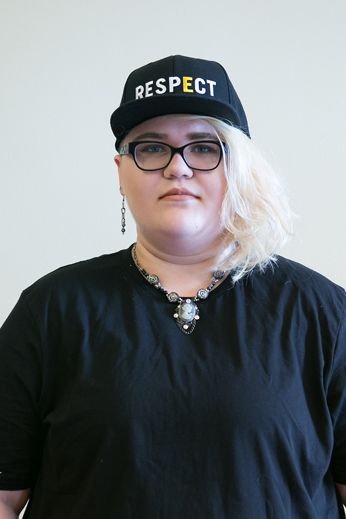 "A student faces the camera proudly wearing the RESPECT Snapback: A black snapback hat with the world RESPECT written across the front in large capitol white letters, and a golden ""E."""