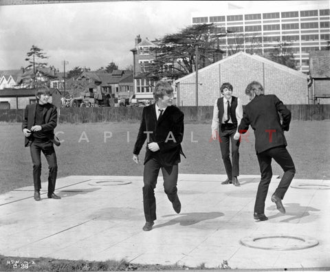 Beatles Group Picture Playing and Dancing on the White Concrete Floor in Black Suit and Vest Premium Art Print