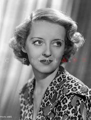 Bette Davis Seated on a Striped Couch in High Neck Short Sleeve Floral Dress and Silk Skirt Premium Art Print