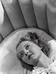 Bette Davis Seated on a White Couch with Arms on the Chair Arm and Hand on the Lap in Black Polka Dot Dress Premium Art Print