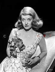 Bette Davis Seated on a Couch with Hand Raised Up in Black Ribbon Top and White Silk Long Dress Premium Art Print