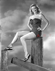 Betty Alexander Posed with Both Hand on the Round Wood Column in Black Striped Short Tube Dress and Flat Sandals Premium Art Print