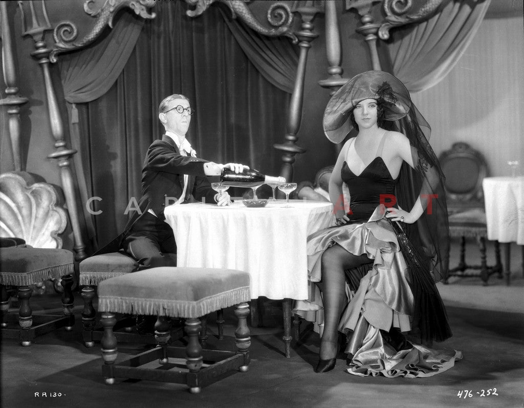 Bebe Daniels Having a Dinner with a Man in Black Strap Dress with Hands Laid on the Waist Premium Art Print