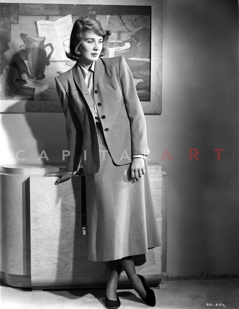 Betsy Drake Posed with Right Hand on the Table Legs Crossed in Grey Suit and Skirt Premium Art Print