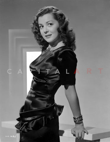 Ann Rutherford Holding on the Table, wearing a Black Dress Premium Art Print
