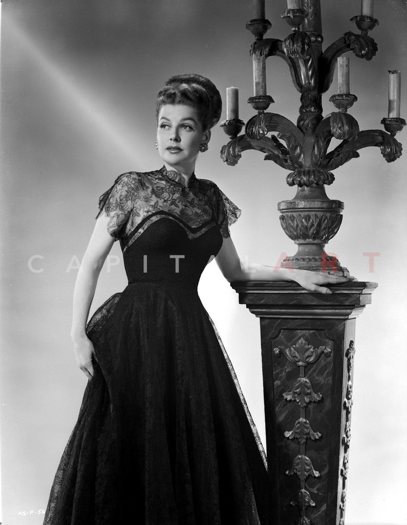 Ann Sheridan wearing a Black Dress while Holding on a Lamp Premium Art Print