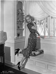 Betty Grable Posed with Hands on Cabinet Doors in Black Ruffled Short Sleeve Dress and Black Ribbon Headband with Black Shoes Premium Art Print