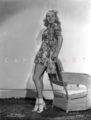 Betty Grable sitting on the Chair with Hand on the Neck in Black Polka Dot Dress and Black Heel Shoes Premium Art Print
