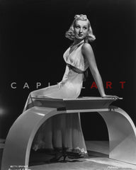 Betty Grable Seated on a Straw Couch in with Hands on the Head in White Strap Sexy Dress and High Heel Shoes Premium Art Print