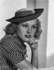 Betty Grable Portrait Looking to the Right with Hands Forward in Black Velvet Hat and Black Polka Dot Short Sleeve Dress Premium Art Print