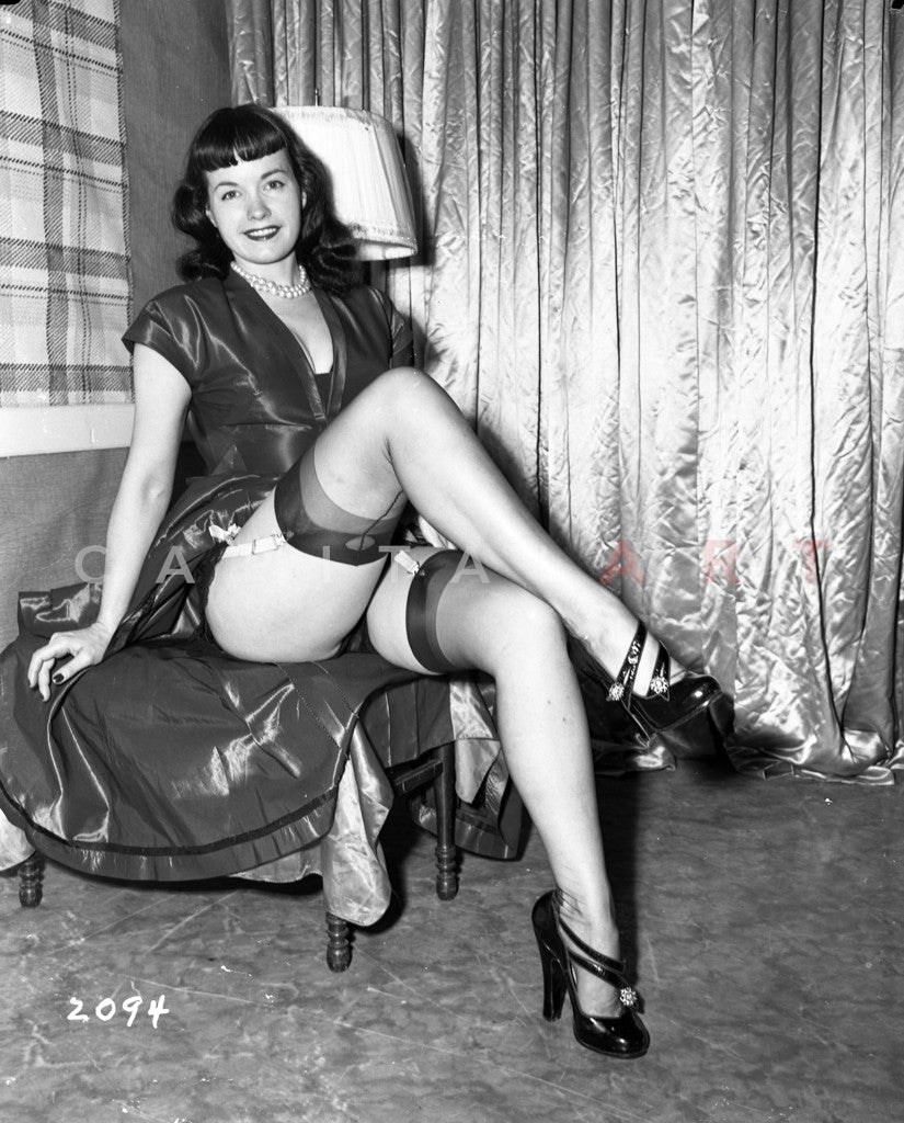 Betty Page Photos: Bettie Page Seated, Legs Crossed Wearing Black Dress With